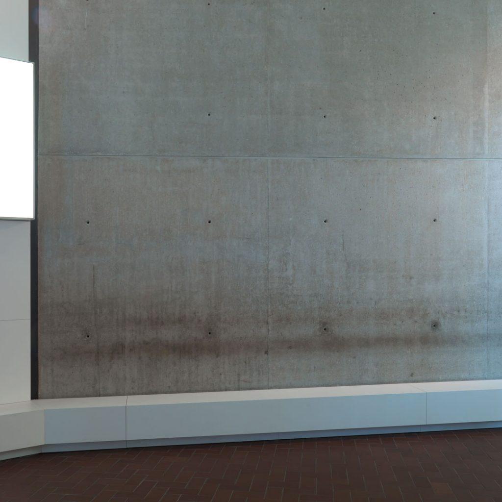 Sitzbank aus weißer Keramik im gelungenen Kontrast zur Sichtbetonwand